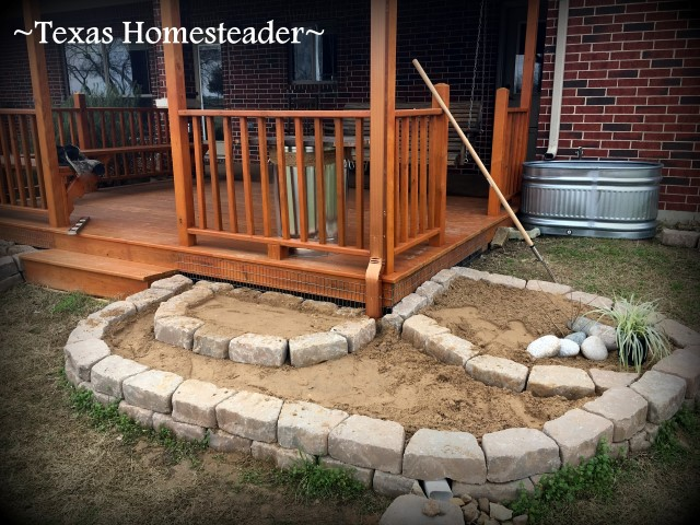 Retaining wall stones and sand footings for support in planting large galvanized water troughs for edible beauty around your home. It's easy and can be done inexpensively too. #TexasHomesteader