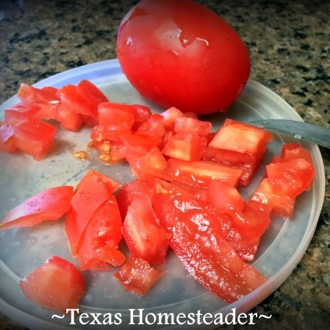 Chopping tomatoes on plastic lid cutting board. This Homestead Hack has 2 benefits when chopping veggies - using something I've already got & keeping juices corralled. #TexasHomesteader