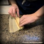 Rolling the tamale. It's time consuming to make homemade tamales. But it's very easy. Come see my step-by-step directions complete with photos and recipe. #TexasHomesteader