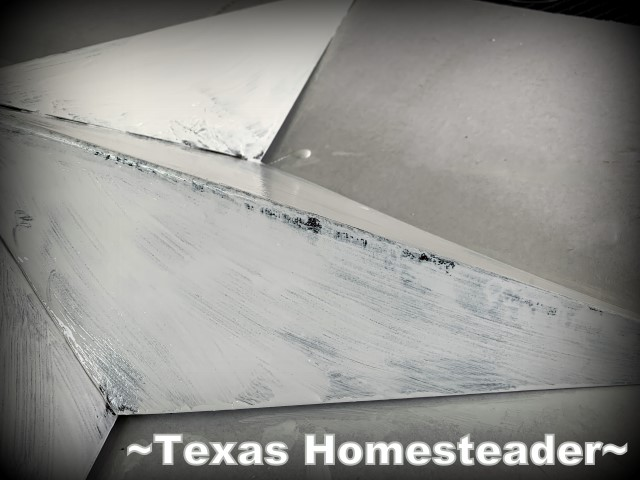 Sandpaper distresses the paint of the metal star. How To Paint A Texas Flag Gate. It was a quick and enjoyable project. And I love the way our gate painted in a Texas flag design looks. #TexasHomesteader